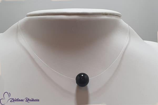 Singel, schwarze fliegende Perle, transparente Kette - eine einzelne Perle