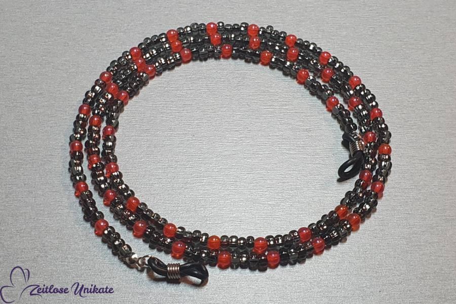 graue Brillenkette mit leuchtend orangen Perlen